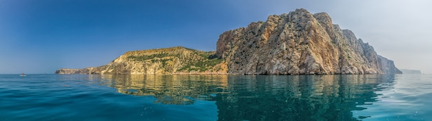 Overzees landschap met jachten en rotsachtige kustlijn