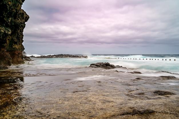 Overzees landschap met rotsen, golven en bewolkte hemel. lange blootstelling foto. spanje, europa,