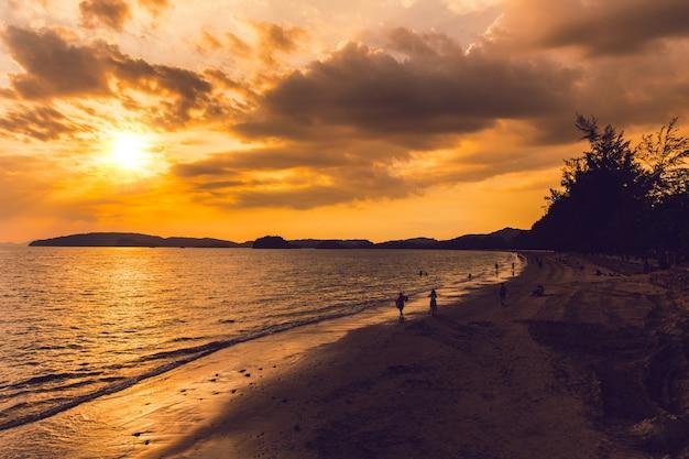 Overzees strand van de oceaanzonsondergang van thailand met mensen op de de vakantieachtergrond van de strandreis.