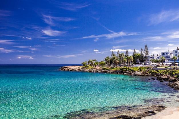 Overzees turkoois water, zandig strand en blauw hemellandschap in vijgeboombaai, cyprus.