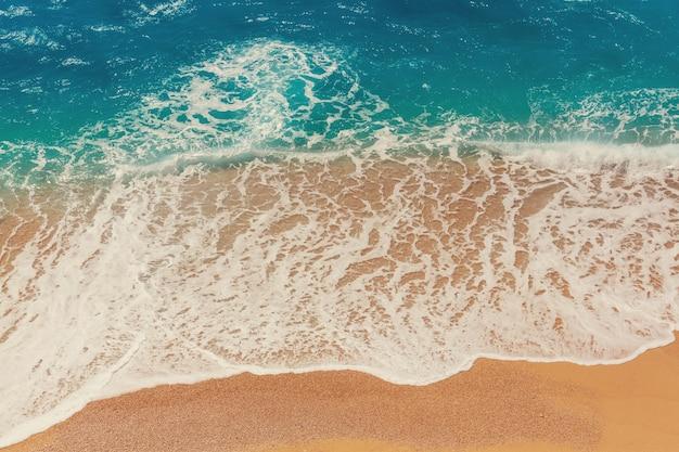 Overzees zandstrand en golf van blauwe oceaan. natuurlijke vakantie achtergrond.