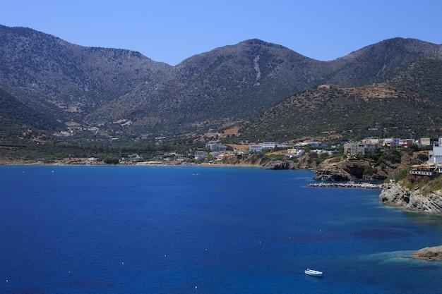 Overzeese baai van vakantieoord bali. uitzicht op de bergen, de kust, gewassen door golven en ligstoelen.
