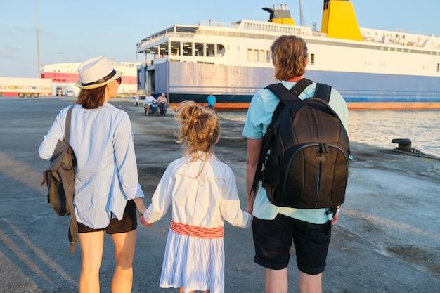 Overzeese familievakantie, moeder, vader en dochterkind in zeehaven
