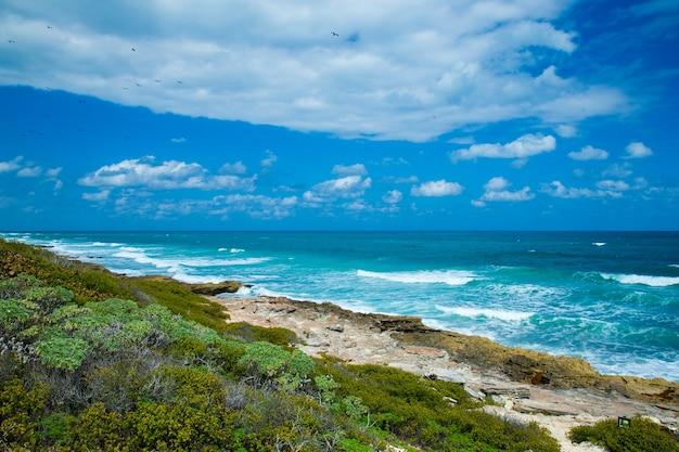 Overzeese golven die over rotsen op wild steenstrand in mexico verpletteren. tropische zee ontspannen