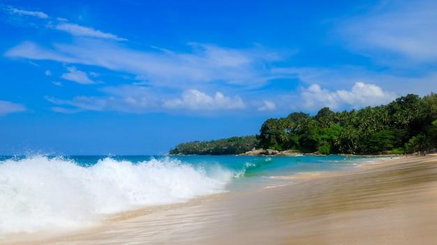 Overzeese golven op het zandstrand in het toeristenseizoen en blauwe hemelachtergrond bij surin strandeiland phuket thailand