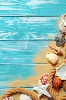 Overzeese kabel met vele verschillende overzeese shells op het overzeese zand op een blauwe houten achtergrond. bovenaanzicht