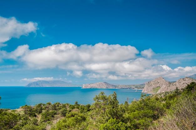Overzeese kust en rotsachtig strand, blauwe hemel met witte wolken, bergen en klein dorp op achtergrond