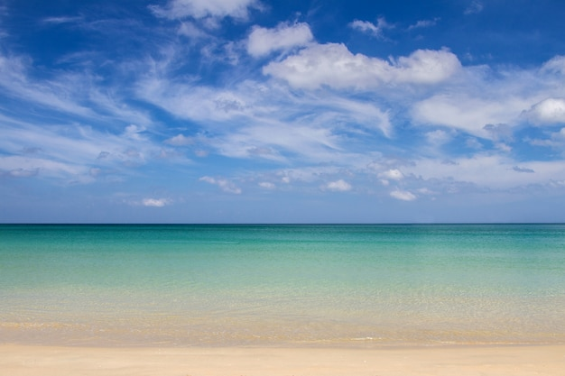 Overzeese zandhemel en zachte golf van blauwe oceaan op de dag van de zandige strandzomer.