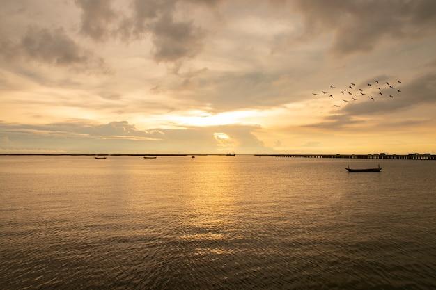 Overzeese zonsondergang in avondtijd met boot en vliegende vogel.
