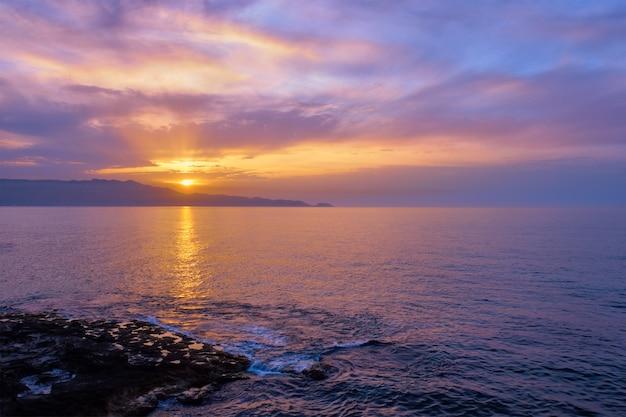 Overzeese zonsondergang met dramatische hemel