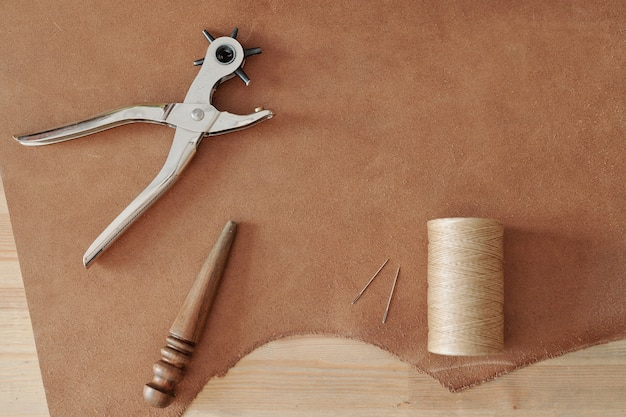 Overzicht handgereedschap voor het maken van gaatjes, klosje met lichte draadjes, twee naalden en houten gereedschap op een deel van beige suede