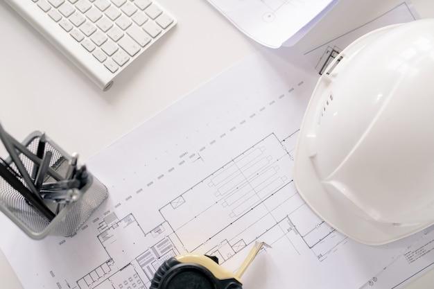Overzicht van benodigdheden van hedendaagse ingenieur op bureau - helm, schetsen, meetlint, potloden en toetsenbord