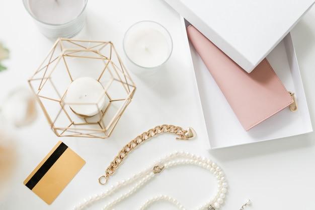 Overzicht van bijou items, plastic kaart, groepje kaarsen en nieuwe nude beige lederen portemonnee in doos op bureau