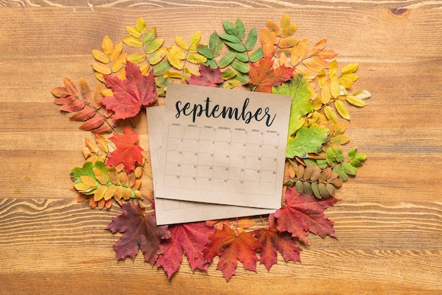 Overzicht van de kalender van september omgeven door kleurrijke herfstbladeren op houten