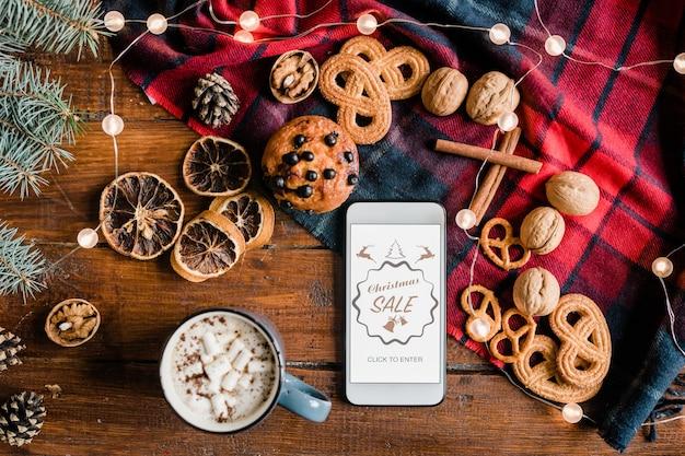 Overzicht van de startpagina van de kerstverkoop van de online winkel op de smartphone, omringd door warme dranken, zoet voedsel en walnoten