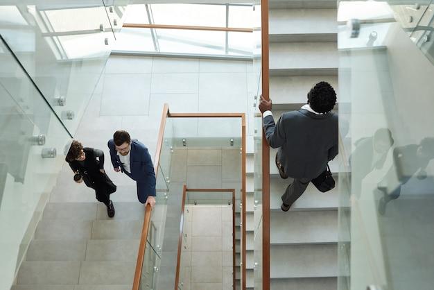 Overzicht van drie jonge interculturele kantoormedewerkers in formele kleding die 's ochtends naar boven gaan terwijl ze zich haasten naar hun werk