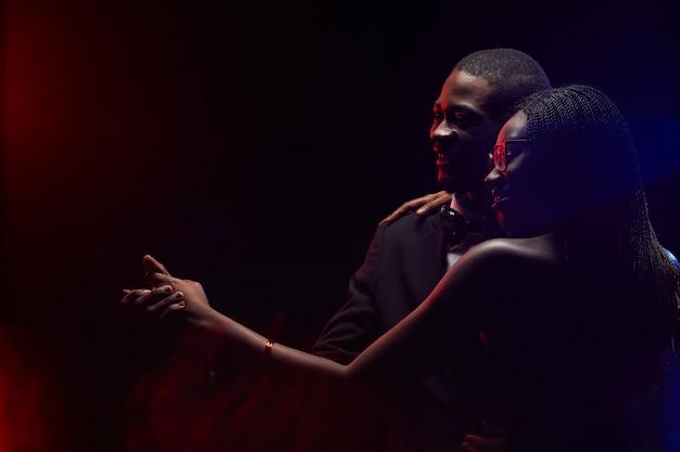 Overzicht van elegant afrikaans-amerikaans paar dat samen in donkere, exemplaarruimte slowdancing