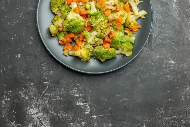 Overzicht van gezonde maaltijd met brocoli en wortelen op een zwarte plaat op grijze tafel
