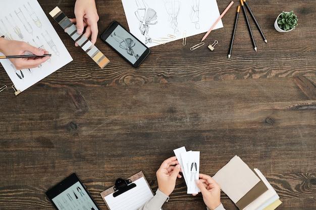 Overzicht van handen van creatieve ontwerpers met kleurstalen en schetsen van nieuwe modellen die werken aan modecollectie door houten tafel