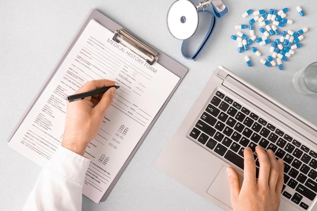 Overzicht van handen van hedendaagse clinicus invullen van medische geschiedenisformulier en toetsen van laptop toetsenbord aanraken terwijl zittend op de werkplek