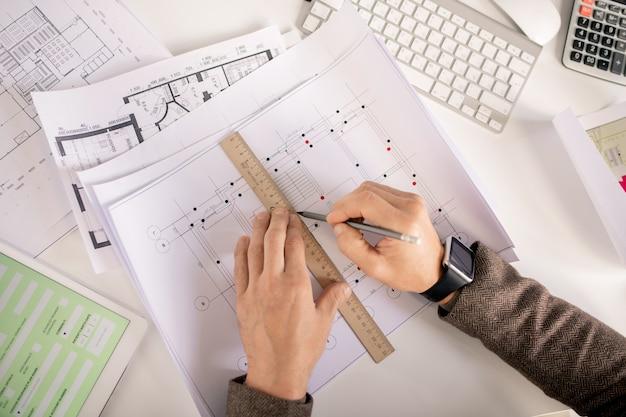 Overzicht van handen van ingenieur of architect met potlood en liniaal tekenlijn tijdens het werken over schets door bureau