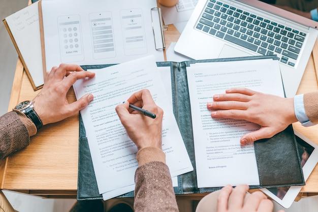 Overzicht van handen van zakenlieden die aan tafel zitten, een van hen vult na onderhandeling persoonlijke gegevens in contract