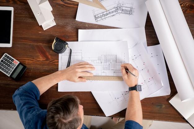Overzicht van hedendaagse ingenieur zittend aan tafel en corrigerende schetsen van architectonische constructies