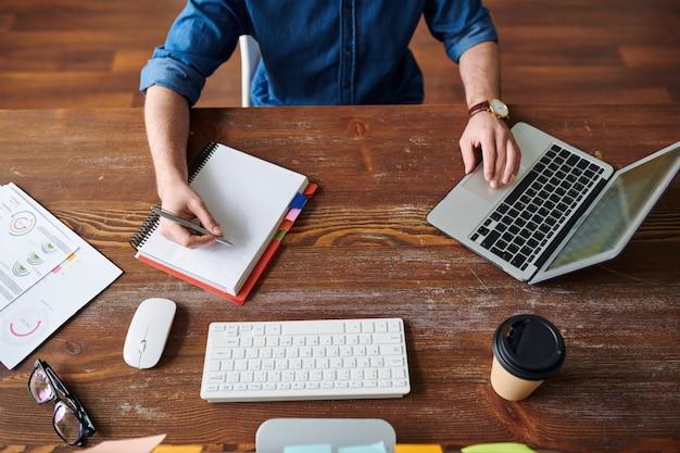 Overzicht van jonge manager of werknemer die aantekeningen maakt in notitieblok tijdens het browsen op het net en het analyseren van online gegevens