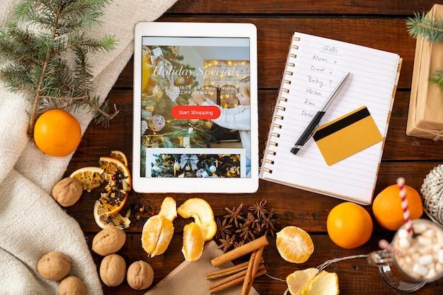 Overzicht van kerstspullen op tafel, creditcard, pen, lijst met mensen om cadeaus voor te kopen en tablet met kerstpromo