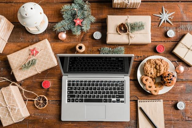 Overzicht van laptop op houten tafel, omringd door geschenken, koekjes en kerstversieringen en symbolen