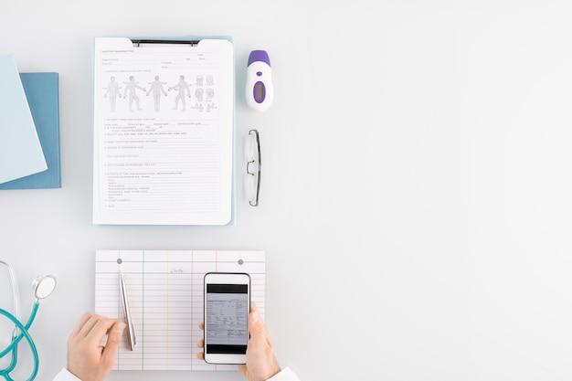 Overzicht van medische werker handen op lege kaart tijdens het scrollen door gegevens in smartphone over werkplek met andere benodigdheden in de buurt