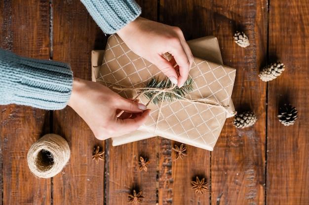 Overzicht van meisje handen bindende knoop bovenop geschenkdoos onder dennenappels en steranijs tijdens het inpakken van geschenken voor vakantie