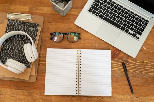 Overzicht van open notebook met blanco pagina's omgeven door laptop, brillen, hoofdtelefoons, blocnotes en pen
