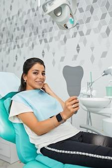 Overzicht van preventie van tandcariës. vrouw aan de stoel van de tandarts tijdens een tandheelkundige ingreep. mooie vrouw glimlach close-up. gezonde glimlach. mooie vrouwelijke glimlach.