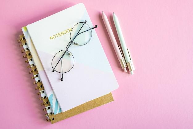 Overzicht van roze tafel met stapel notitieboekjes, brillen en twee pennen zonder mensen in de buurt