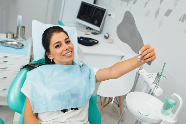 Overzicht van tandcariës preventie. vrouw op de stoel van de tandarts tijdens een tandheelkundige ingreep mooie vrouw glimlach close-up. gezonde glimlach. mooie vrouwelijke glimlach.