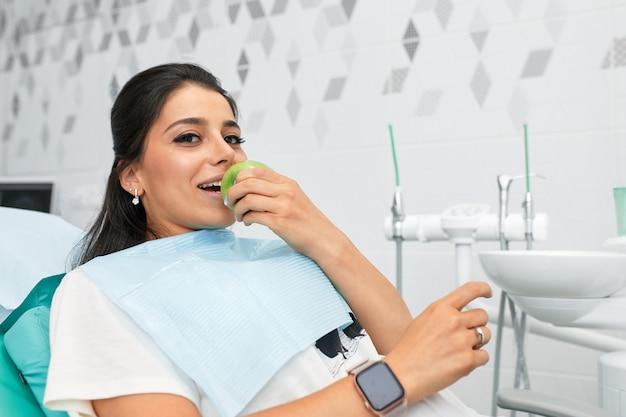 Overzicht van tandcariës preventie vrouw op de stoel van de tandarts tijdens een tandheelkundige ingreep mooie vrouw glimlach close-up