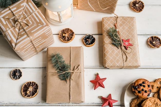 Overzicht van verpakte geschenkdozen, decoratieve schijfjes citroen, rode sterren, lantaarn en koekjes voor gasten op witte tafel