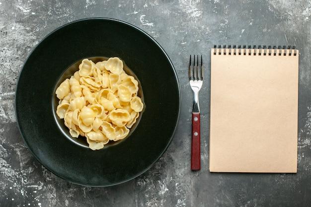 Overzichtsmening van heerlijke conchiglie op een zwarte plaat en een mes naast notitieboekje op grijze achtergrond