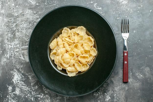 Overzichtsweergave van heerlijke conchiglie op een zwarte plaat en mes op grijze achtergrond