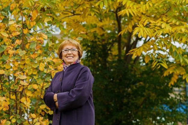 Oyful portret van een volwassen vrouw met bril in het park in het herfstseizoen een glimlachende dame van middelbare leeftijd met een positieve optimistische blik