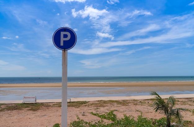 P-teken in cirkelverkeerssymbool voor parkeren dichtbij strandmening met heldere bewolkte blauwe hemel. zonnige dag. zomervakantie.