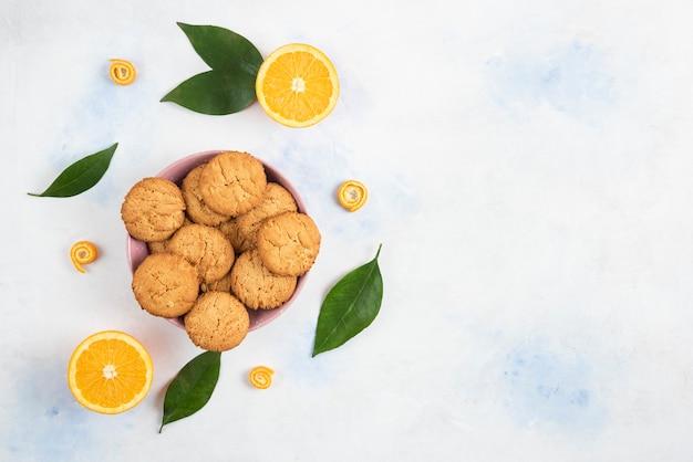 P weergave van zelfgemaakte koekjes op een houten bord en verse, sappige sinaasappelen met verlof op witte achtergrond.