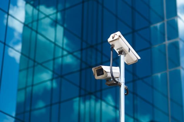 Paal met twee witte videobewakingscamera's bij groot kantoorglasgebouw