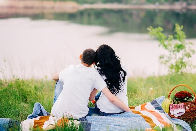 Paar achterover te leunen op de natuur. zomerpicknick bij zonsondergang