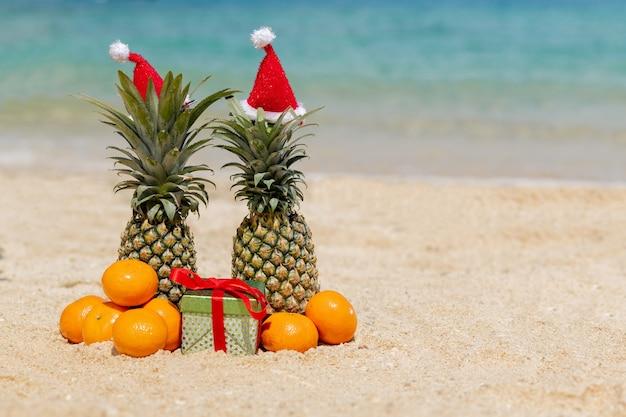 Paar ananas in rode kerstmuts op het strand.
