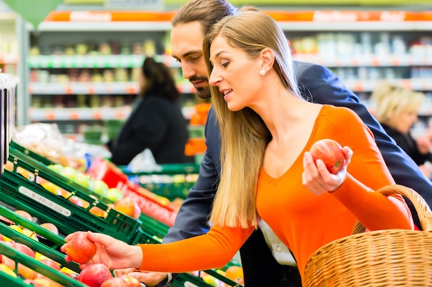 Paar appels selecteren tijdens het winkelen in de supermarkt
