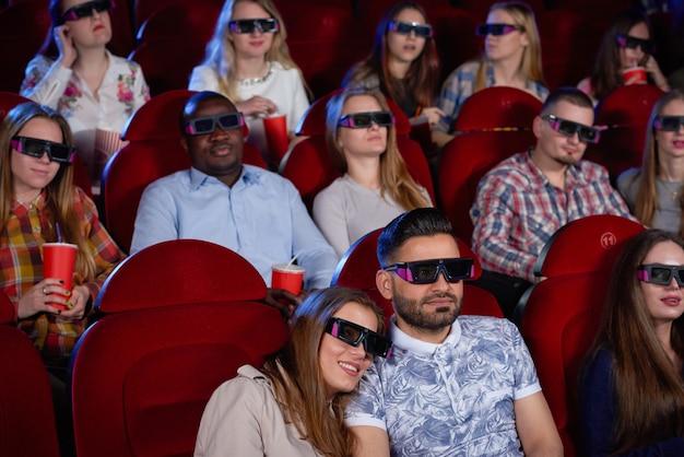 Paar arabische man en brunette vrouw zitten samen in de bioscoop, omarmen en kijken naar komedie.
