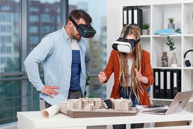 Paar architecten of ingenieurs bij vr-bril die werken met mockup van toekomstige woonwijk in modern kantoor