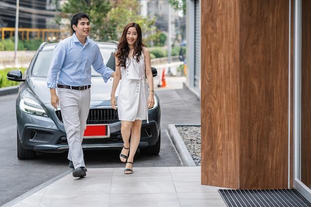 Paar aziaat die in de autotoonzaal lopen voor het controleren van hun grijze kleurenauto